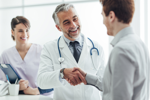 Doctors Shaking Businessperson Hand